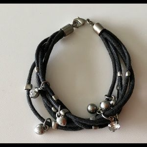 Celtic style necklace and black bracelet.